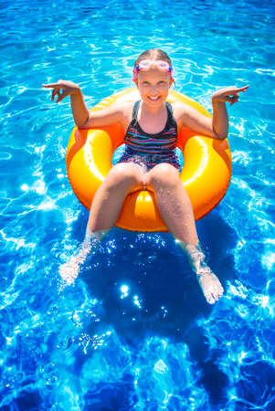 Young girl sitting and smiling in inflatable ring on water ocean. Summer vacations concept.