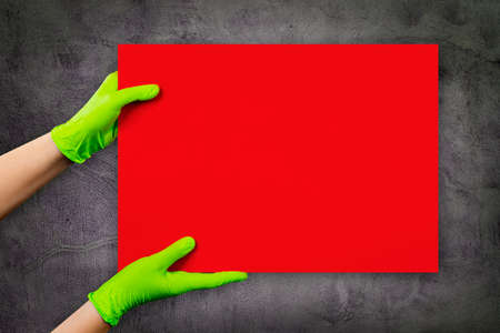 Empty red card in doctor's hands in green gloves with copy space, on grey cement grunge wall. Reklamní fotografie
