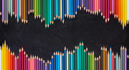 Wave border of colorful wooden pencils on a blank blackboard, back to school concept.