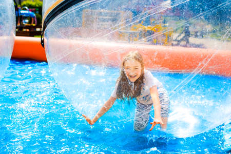 Young girl playing inside a floating water walking ball in pool.