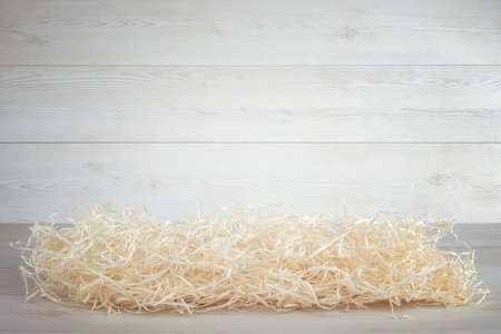 Straw packing material on white wooden wall background. Stock Photo