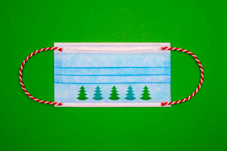 Blue medical face mask with red and white christmas ribbon instead of rubber and green christmas tree on green paper background. Flat lay.Covid during Christmas season concept. Stock Photo