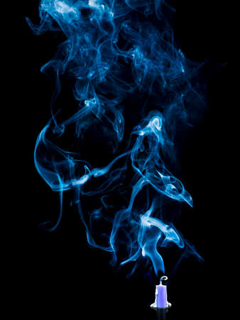 Detail of the blowed out candle with the smoke from the wick over black background Stock Photo
