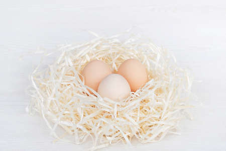 Raw organic brown and white eggs in nest made of staw shreded paper.