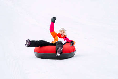 Child girl on snow tubes downhill at winter day. Stock Photo