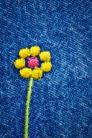 Embroidered flower on fragment of blue denim jeans texture