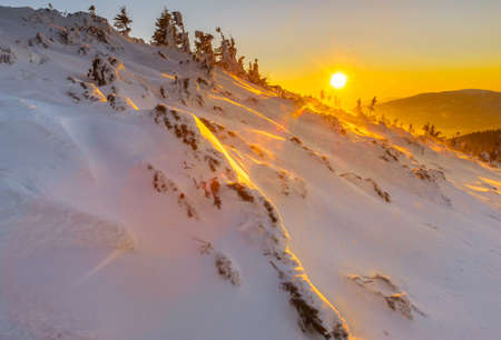 Winter sunset in the mountains and surface of snow