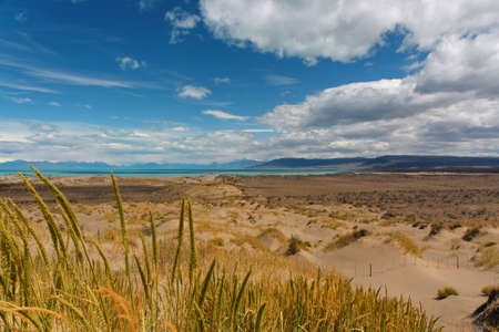 Wide landscape Desert overlooking the lake, dunes and grass in the foreground
