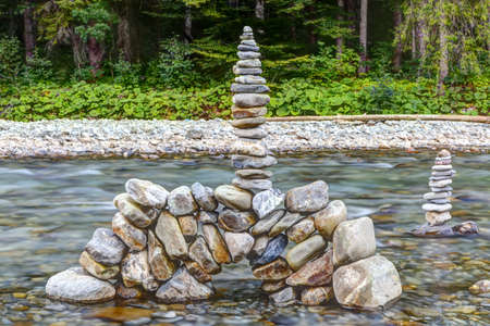 statics: Stone tower in the mountain river in the evening light is Stock Photo