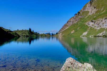 Lake in high mountains in the Alps in summer photo