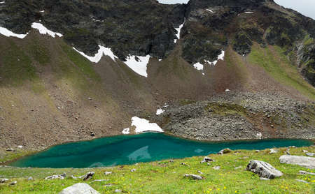 greenish blue: Greenish translucent lake in the mountains of the Alps in the summer.