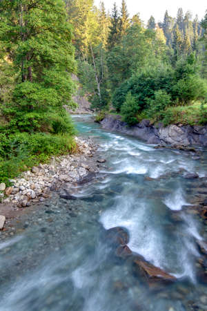 spiritually: Alps, mountain river in the morning light as HDR shooting. Flowing water in long exposure.