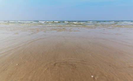 is cloudless: Waves on the sandy beach of the North Sea coast, with the horizon and cloudless sky.