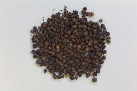 peppercorns: Black dried whole, milled raw peppercorns on plate.