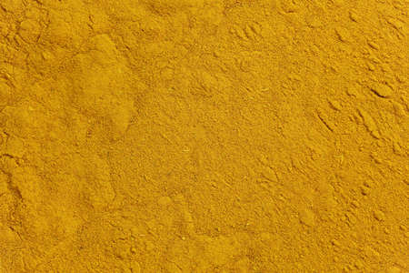 A layer of ground turmeric was with yellowish coloring, background Imagens