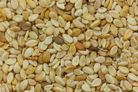 untreated: Close up of different bright, untreated sesame seeds. Stock Photo