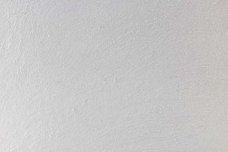 White rustic wall, painted with granules of sand.