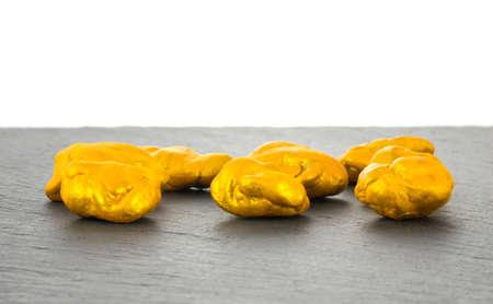 Golden nuggets on dark background. 免版税图像