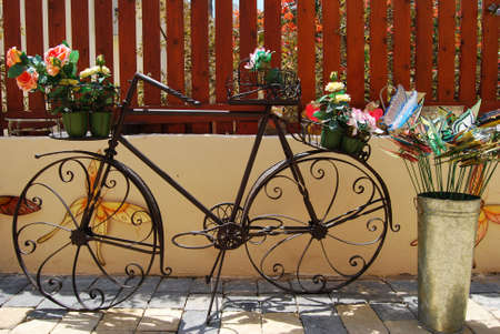 Vintage old black bicycle with flowers in the front basket photo
