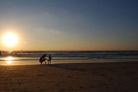 young woman with small child on the sea shore on sunset photo