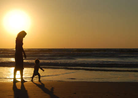 destin: young woman with small child on the sea shore on sunset Stock Photo