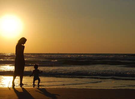 jeune femme avec le petit enfant sur le rivage de mer sur le coucher du soleil Banque d'images - 2406459