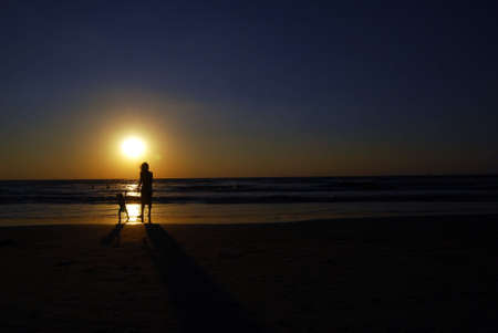 young woman with small child on the sea shore on sunset Stock Photo - 2406460