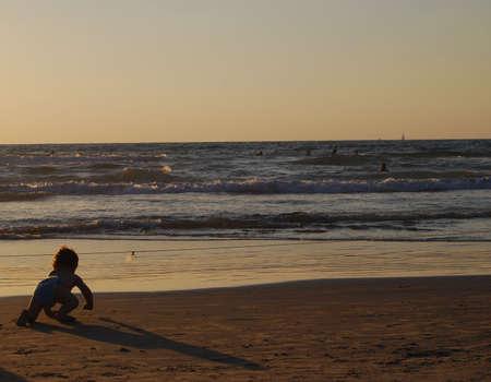 small child on sea on sand in sunset photo