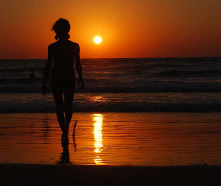 siluet beautiful woman on sea and the sunset of sun photo