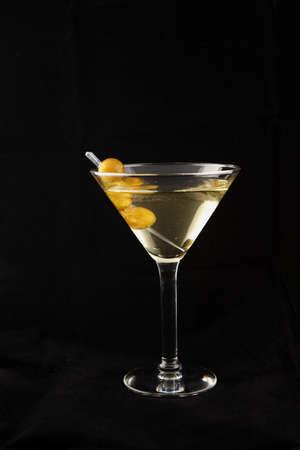 yellow martini cocktail with elegante olive decoration Banco de Imagens