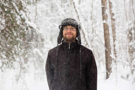 Man in fur winter hat with ear flaps smiling portrait