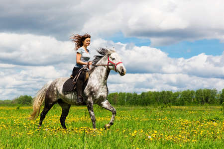 Woman riding on a gray horse in the field