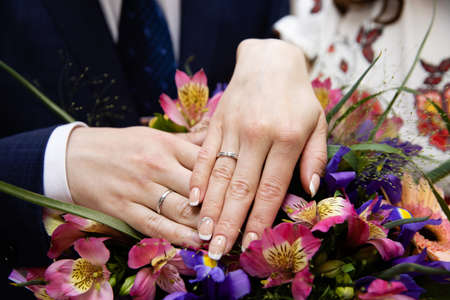 Hands of the groom and bride with rings and bridal bouquet Stockfoto - 104731395