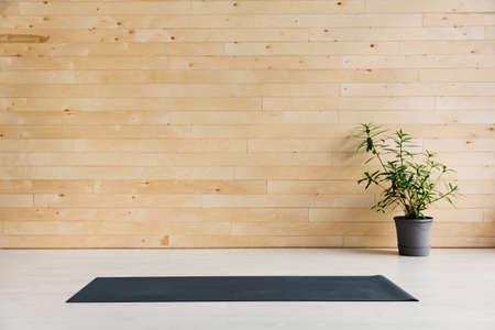 Leere Yogamatte auf dem Boden. Ausrüstung für Yoga. Konzept gesunder Lebensstil Standard-Bild