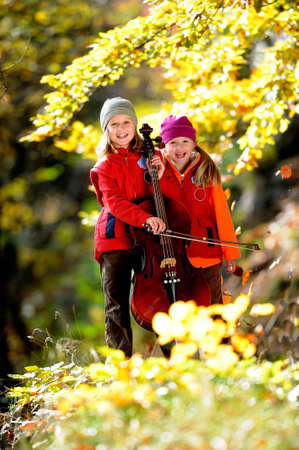 violoncello: Young musicians autumn forest Stock Photo