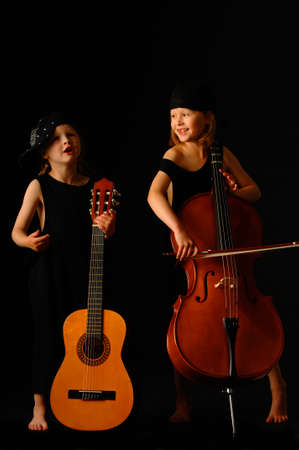 School aged girls with cello and guitar on black background photo