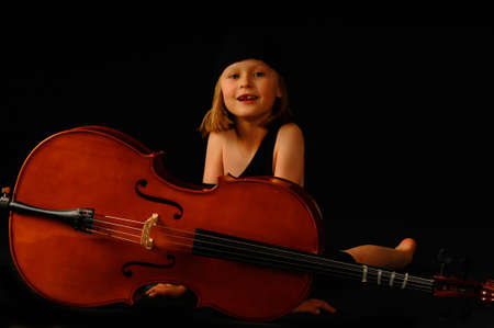 School aged girl with cello on black background photo