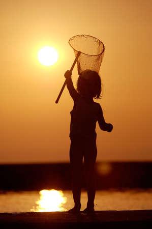 redes de pesca: Chica de pesca en la puesta de sol en la orilla del lago