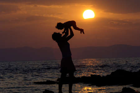 Mother Holding Kid In The Sunset on The Sea Coast photo