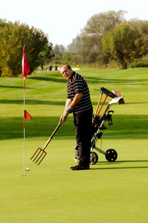 Funny Male Golfer Playing Golf With Pitchfork photo