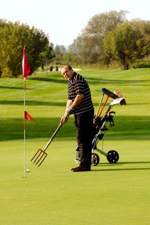 Lustiger männlicher Golfspieler, der Golf mit Pitchfork spielt