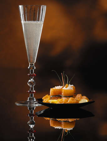 Glass of Champagne and Salmon Rolls With Reflection on Abstract Background photo