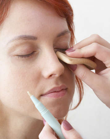 suntanned: beautician is doing make-up to red-haired woman