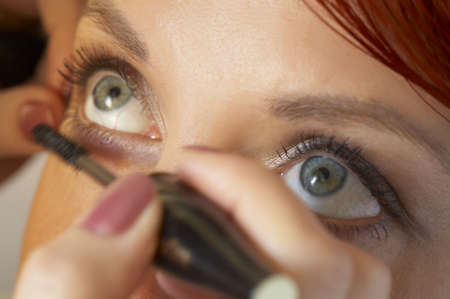 decent: beautician is doing make-up to red-haired woman