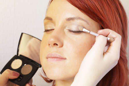 cosmetologist: beautician is doing make-up to red-haired woman