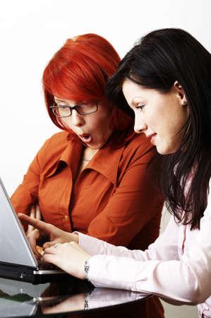Two beautiful caucasian businesswomen are very surprised photo