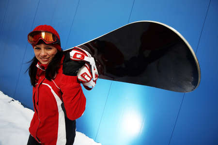 A lifestyle image of a young adult female (age 20-25) snowboarder. photo