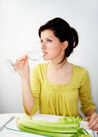young woman having her breakfast with water and celery photo