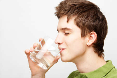 gauzy: young handsome man is drinking mineral water