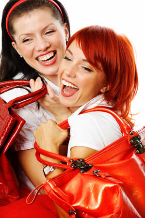 careless: two young smiling women with red handbags Stock Photo
